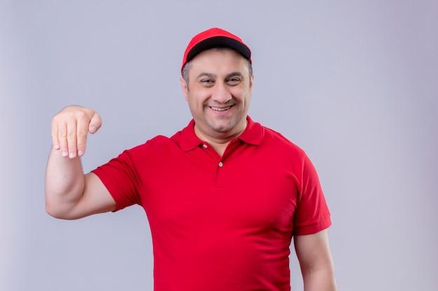 Доставщик в красной форме и кепке жестикулирует рукой, улыбаясь, концепция языка тела стоит на белом