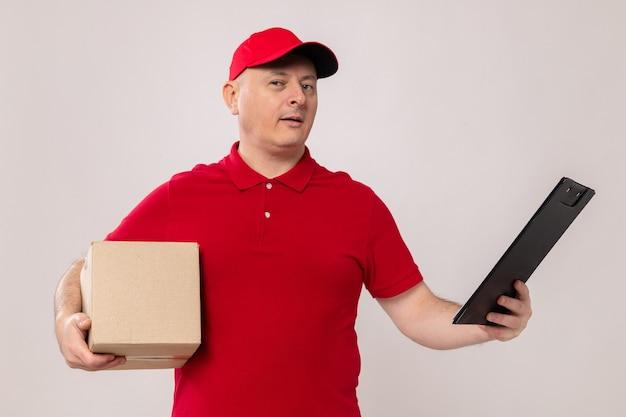 白い背景の上に立って自信を持って笑顔のカメラを見て段ボール箱とクリップボードを保持している赤い制服と帽子の配達人