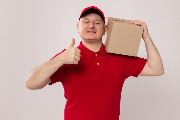 Доставщик в красной форме и кепке держит картонную коробку на плече, уверенно улыбаясь, показывая большие пальцы руки вверх, стоя на белом фоне