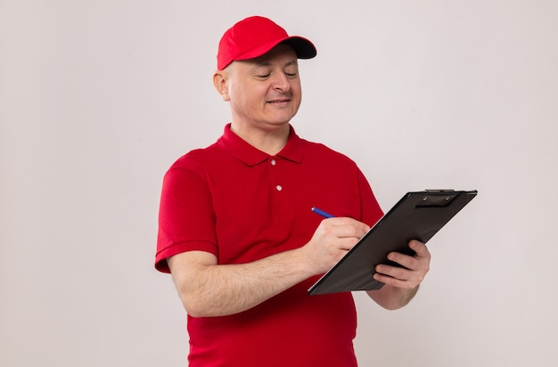 赤い制服を着た配達人とクリップボードとペンを保持し、白い背景の上に立って自信を持って笑顔のメモを作る