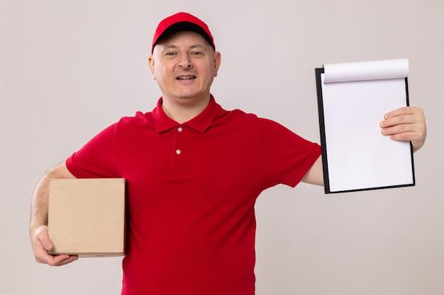 빨간색 유니폼을 입은 배달원과 빈 페이지가 있는 클립보드를 들고 있는 모자와 흰색 배경 위에 유쾌하게 행복하고 긍정적인 서 있는 카메라를 바라보는 마분지 상자