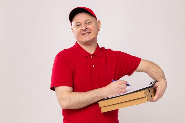 Доставщик в красной форме и кепке держит коробки для пиццы и буфер обмена с пустыми страницами и ручкой, весело улыбаясь