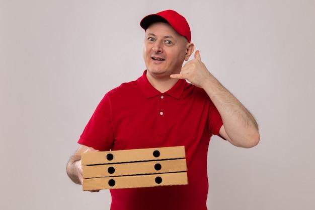 赤い制服を着た配達人とピザの箱を持ってカメラを見て幸せで前向きな笑顔で白い背景の上に立っているジェスチャーを呼んでください