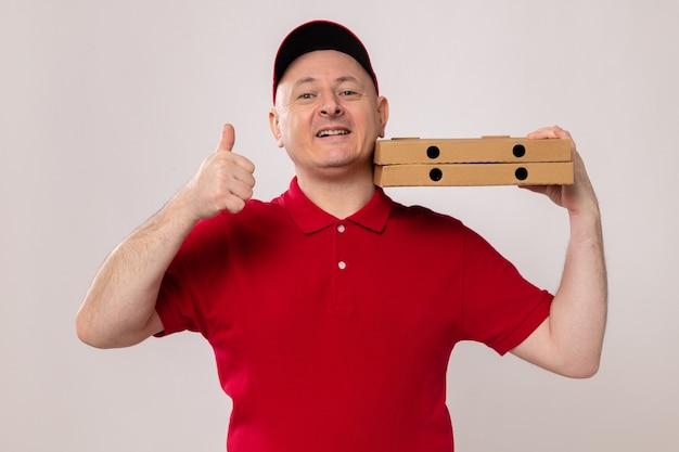 Доставщик в красной форме и кепке держит коробки для пиццы, выглядит счастливым и позитивно улыбается, весело показывает палец вверх