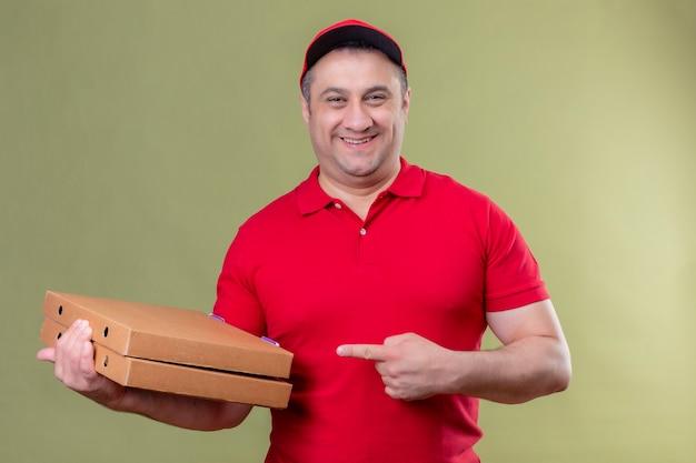 Доставщик в красной форме и кепке держит коробки с пиццей, указывая на них указательным пальцем, уверенно улыбаясь, с счастливым лицом, стоящим над зеленой зоной