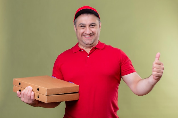Доставщик в красной форме и кепке держит коробки для пиццы позитивно и счастливо улыбается, весело показывает палец вверх, стоя над зеленой зоной