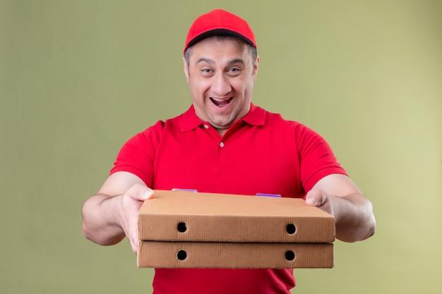 赤い制服を着た配達人とピザボックスを押しながらカメラを伸ばして分離された緑の上に立って幸せそうな顔で元気に笑顔