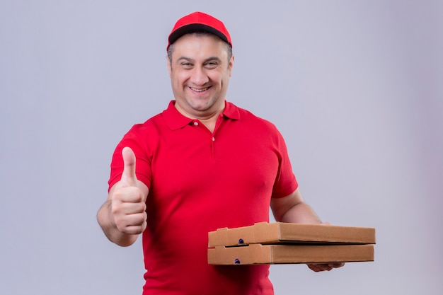 赤い制服と分離の白いスペースの上に立って親指を示す幸せそうな顔でピザの箱を保持しているキャップの配達人