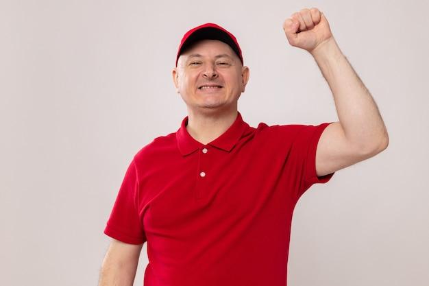흰색 배경 위에 서 있는 승자처럼 행복하고 자신감 있게 주먹을 들고 카메라를 바라보는 빨간 유니폼과 모자를 쓴 배달원