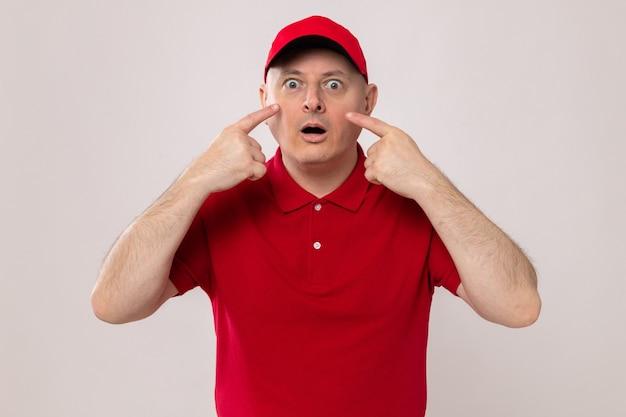 Курьер в красной форме и кепке выглядит удивленным, указывая указательными пальцами на глаза