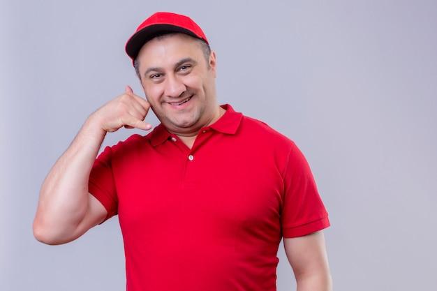 赤い制服を着た配達人と白で立ってジェスチャーを呼んで元気よく笑ってキャップ