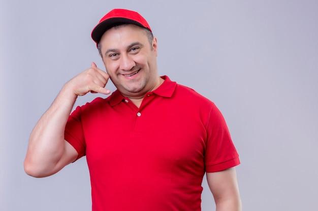 赤い制服を着た配達人とキャップジェスチャー立って私を元気よく笑ってキャップ