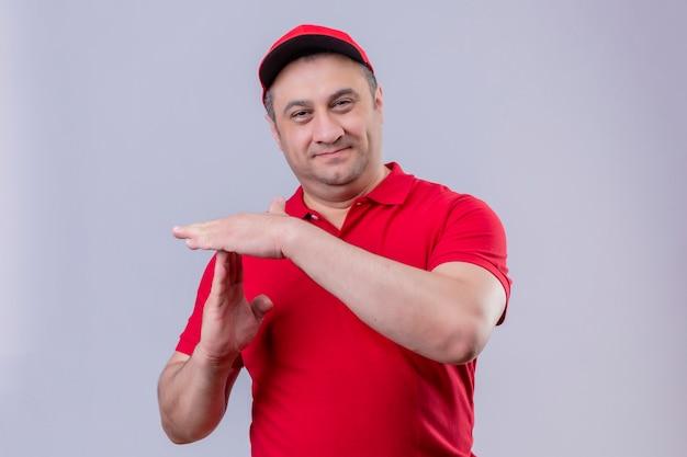 Доставщик в красной форме и кепке улыбается, делая жест тайм-аута на белом