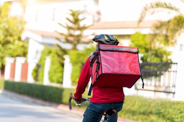 赤い制服を着た配達員が自宅の顧客に商品を配達するサイクリング。