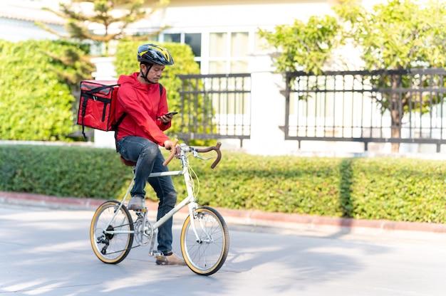 빨간색 유니폼 배달 남자 집에서 고객에게 제품을 제공하기 위해 사이클링.
