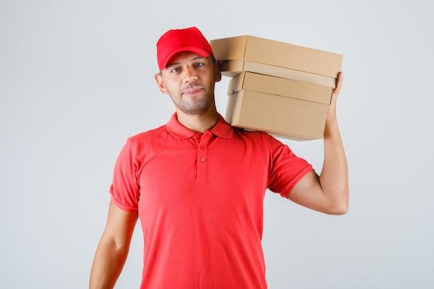 Доставщик в красной форме держит картонные коробки на плече