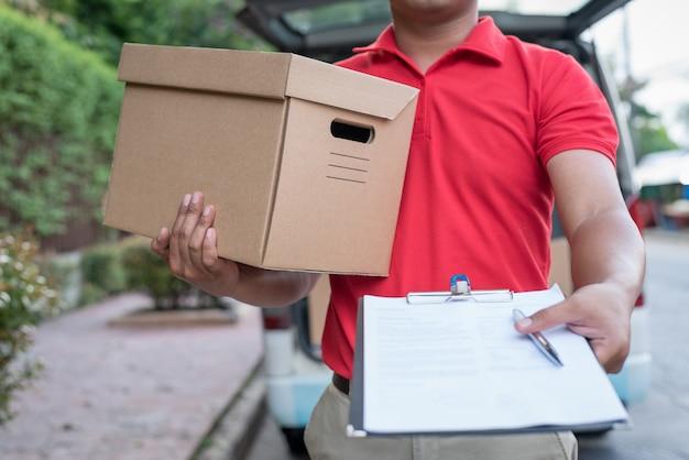 クリップボードを保持している赤い制服を着た配達人