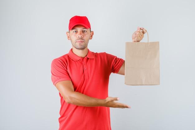 Доставщик в красной форме держит бумажный пакет