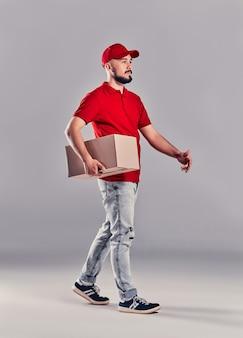 Экспедитор в красной форме, изолированные на сером фоне, студийный портрет. сотрудник-мужчина в принте футболки кепки, работая как дилер-курьер, держит пустую картонную коробку. концепция обслуживания. копировать пространство для копирования