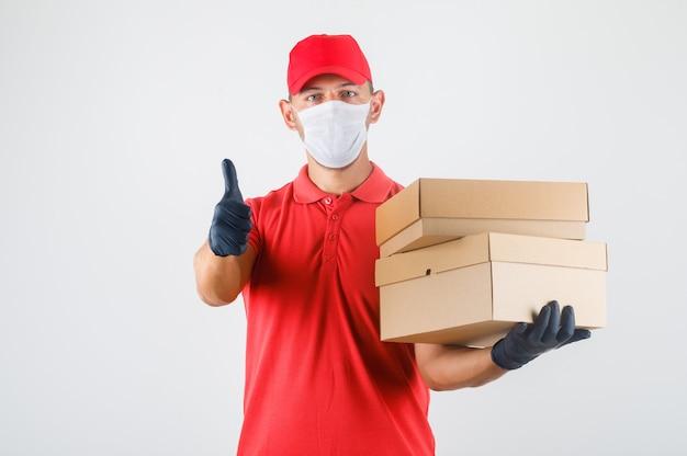 Курьер в красной форме, медицинской маске, перчатках держит картонные коробки и показывает палец вверх