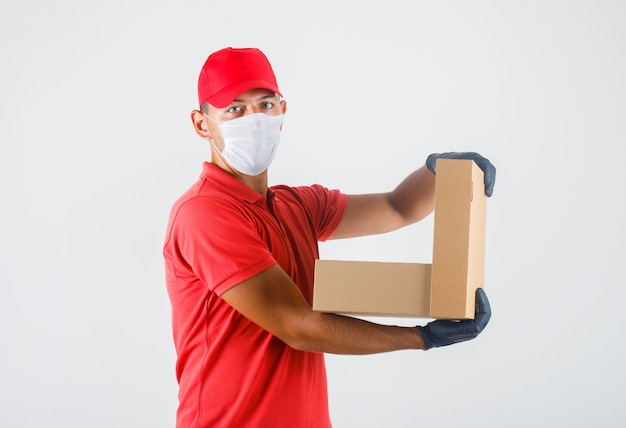 Курьер в красной форме, медицинской маске, перчатках держит открытую картонную коробку