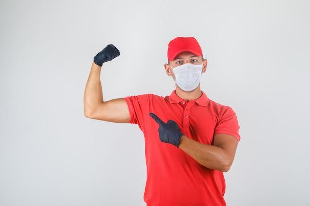 Курьер в красной форме, медицинской маске, перчатках показывает бицепсы и выглядит мощным