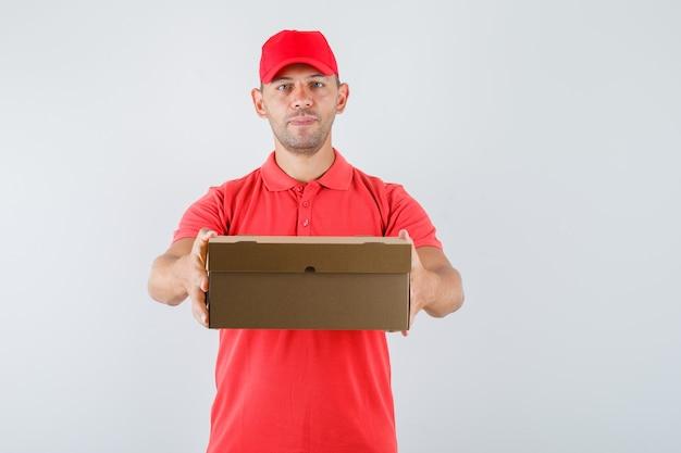 Доставщик в красной форме, показывая картонную коробку