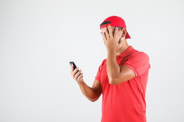 Доставщик в красной форме с помощью смартфона с рукой на лице и осторожным взглядом