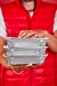赤いベストの制服を着た配達員は、ボックスフード、配達サービス、テイクアウトレストランの家のドアへのフードデリバリーを保持します
