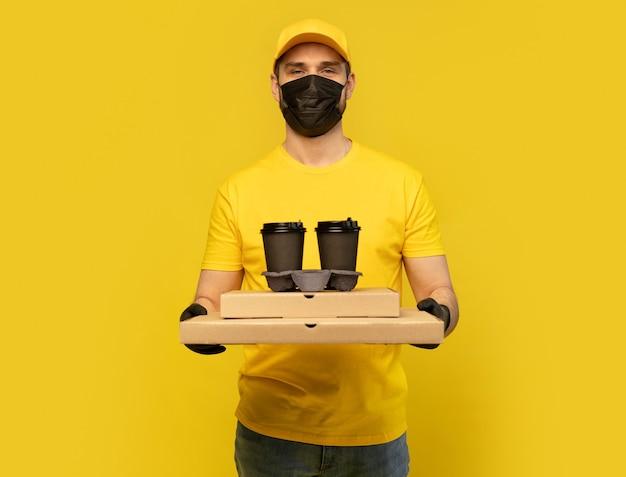 Курьер в желтой кепке, форме футболки, маске, изолированных перчатках. парень держит чашку кофе на вынос