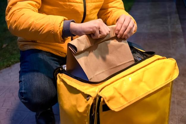 黄色いジャケットの配達人が黄色いバックパックを開けて、注文でバッグを取る