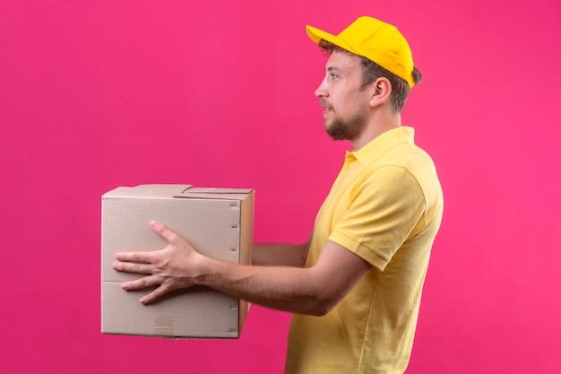 黄色のポロシャツとピンクの横に立っている顧客に大きな段ボール箱を与えるキャップの配達人