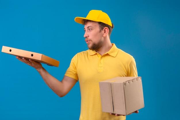 Доставщик в желтой рубашке поло и кепке держит коробку с упаковкой и дает коробку для пиццы покупателю, уверенно выглядящему, стоящему на синем