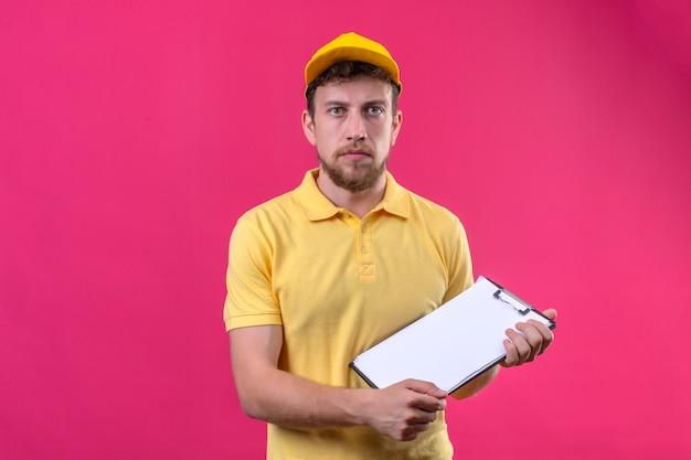 黄色のポロシャツとピンクの笑顔で立っていない深刻な顔でカメラを見て手でクリップボードを保持しているキャップの配達人