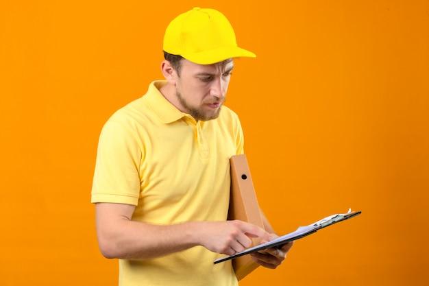 Курьер в желтой рубашке поло и кепке держит в руках буфер обмена и читает что-то с серьезным лицом, стоя на изолированном оранжевом