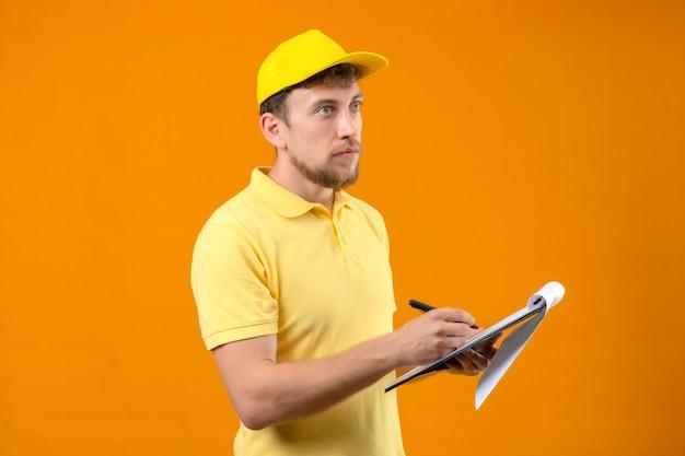 Курьер в желтой рубашке поло и кепке держит в руках буфер обмена и пишет что-то серьезным лицом, стоящим боком на оранжевом Бесплатные Фотографии