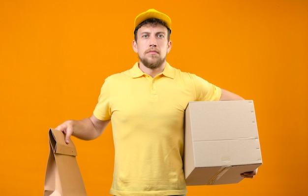 Курьер в желтой рубашке поло и кепке держит большую картонную коробку и бумажный пакет, глядя в камеру с серьезным лицом, стоящим на оранжевом