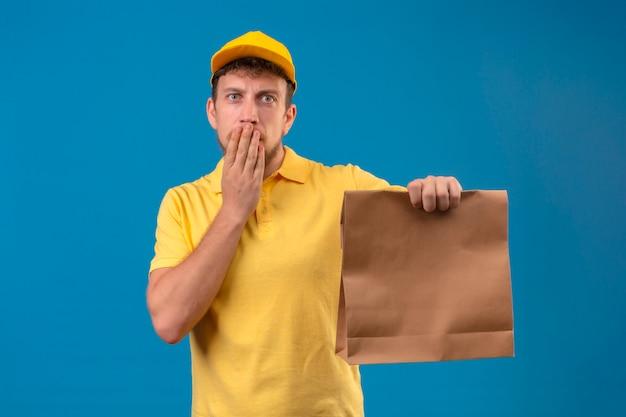 Курьер в желтой рубашке поло и кепке держит бумагу с удивленным ртом и рукой, стоящей на синем