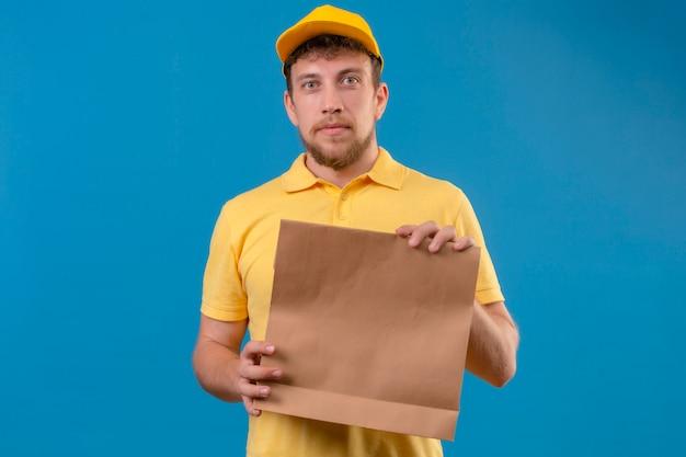 노란색 폴로 셔츠와 격리 된 파란색에 서 심각한 얼굴로 카메라를 찾고 종이 패키지를 들고 모자 배달 남자