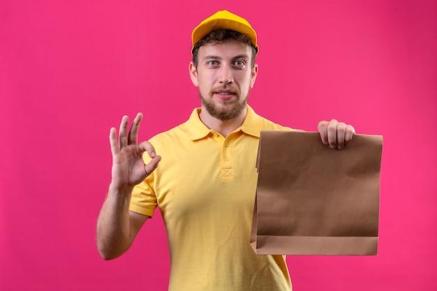노란색 폴로 셔츠와 모자 종이 패키지를 들고 배달 남자는 고립 된 분홍색에 서있는 확인 서명을하고 친절한 미소