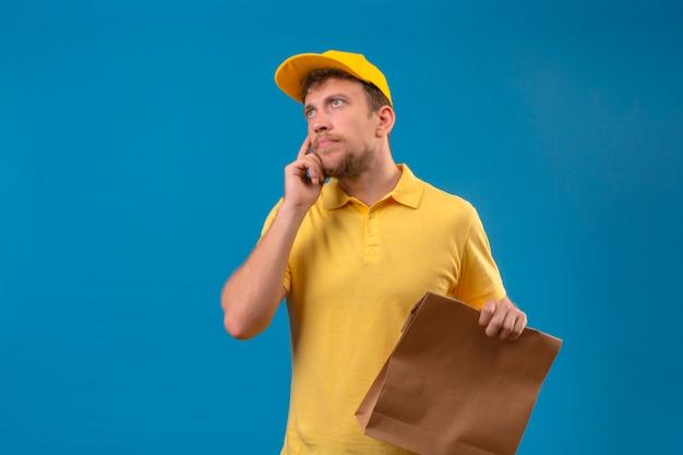 노란색 폴로 셔츠와 격리 된 파란색에 잠겨있는 모습을 생각 찾고 턱에 손으로 서 종이 패키지를 들고 모자 배달 남자