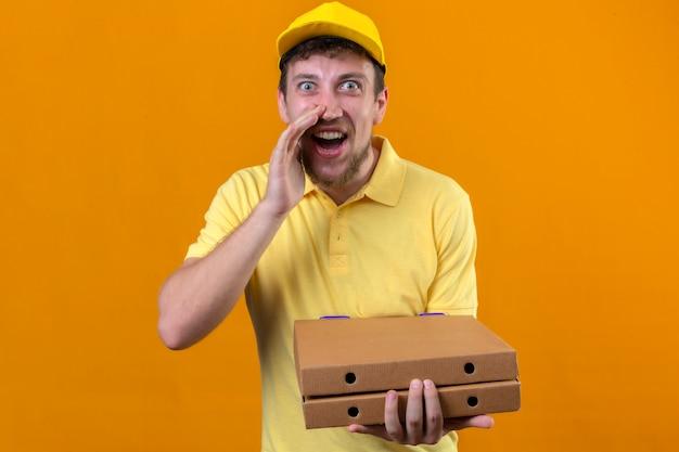 黄色のポロシャツとピザの箱を保持している配達人