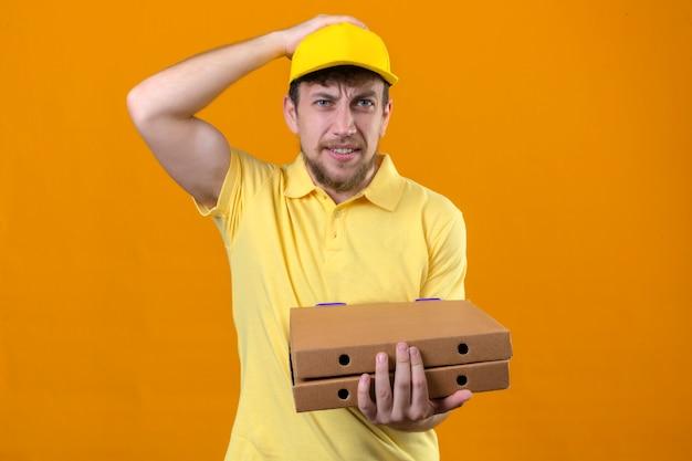 黄色のポロシャツとピザの箱を手で立っているミスの配達人は間違いのための頭の上に手で立っているエラーを覚えている分離のオレンジの悪い記憶概念を忘れてしまった