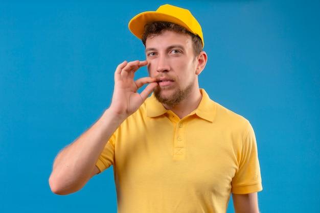 Курьер в желтой рубашке поло и кепке делает жест молчания, как будто закрывает рот молнией на изолированном синем