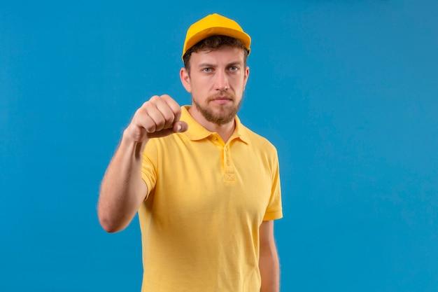 黄色のポロシャツとキャップ分離の青を脅かす渋面でカメラに拳を示す配達人