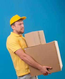 Курьер в желтой рубашке поло и кепке стоит с большими картонными коробками и страдает от тяжелого веса на синем