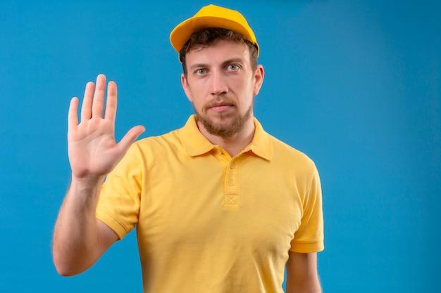 Курьер в желтой рубашке поло и кепке, стоящий с открытой рукой, делает знак остановки с серьезным и уверенным выражением защитного жеста на изолированном синем
