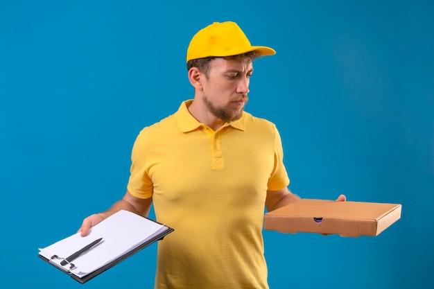 黄色のポロシャツとピザの箱と青にしかめっ面でクリップボードを手に立っているキャップの配達人