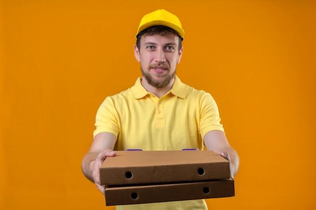 Курьер в желтой рубашке поло и кепке протягивает коробки из-под пиццы, дарит покупателю дружелюбно улыбающийся на изолированном апельсине