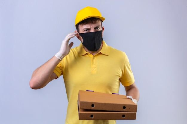 노란색 폴로 셔츠와 격리 된 흰색에 귀 근처에 손가락으로 서 듣기 어려운 피자 상자를 들고 검은 보호 마스크를 쓰고 모자 배달 남자